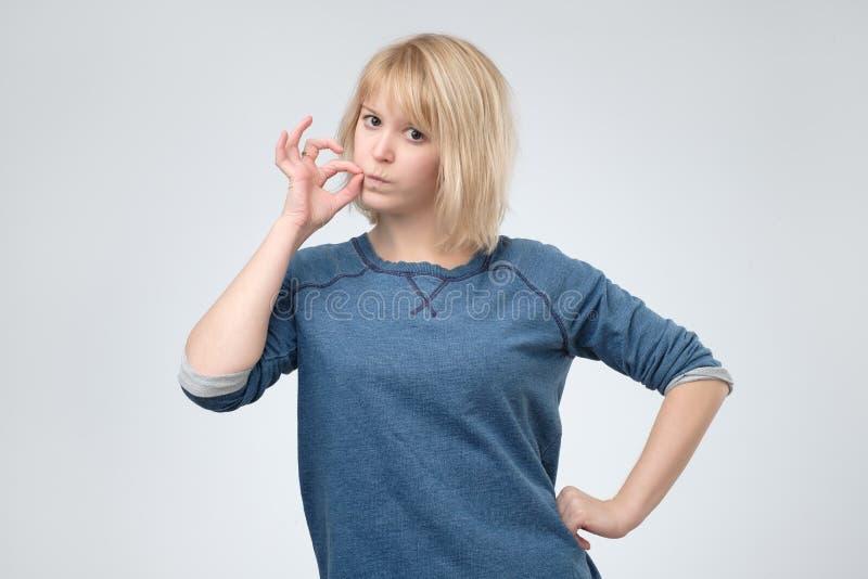 Gardez un secret, femme fermant la fermeture éclair sa bouche fermée photo stock