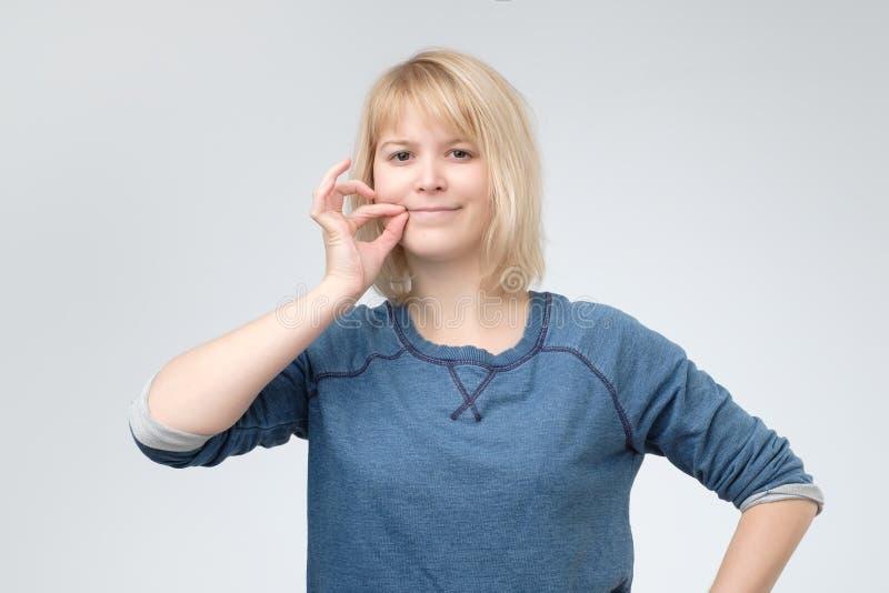 Gardez un secret, femme fermant la fermeture éclair sa bouche fermée photographie stock