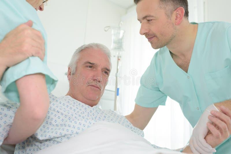 Gardien aidant le patient supérieur dans le lit images libres de droits