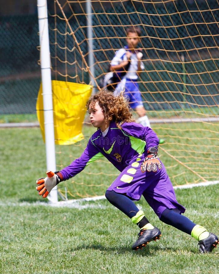 Gardien de but du football du football de la jeunesse allant chercher les économies photo stock