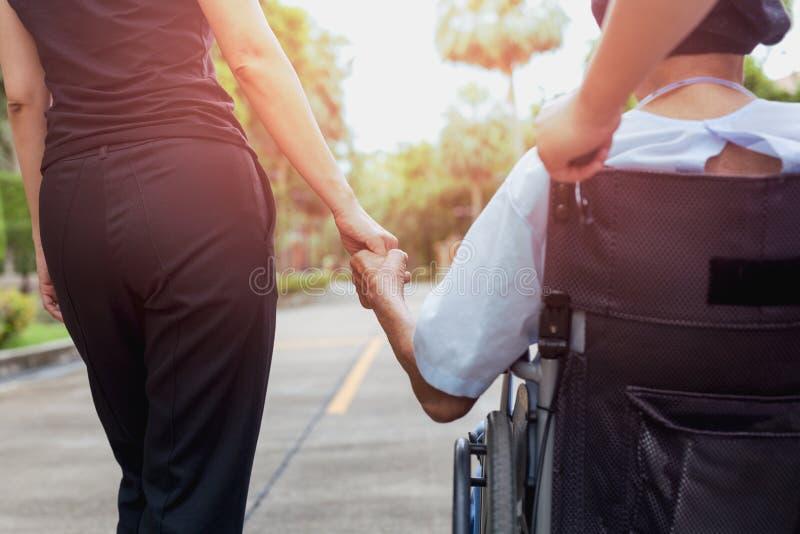 Gardien et fille passant le temps extérieur avec le patient dans le fauteuil roulant images stock