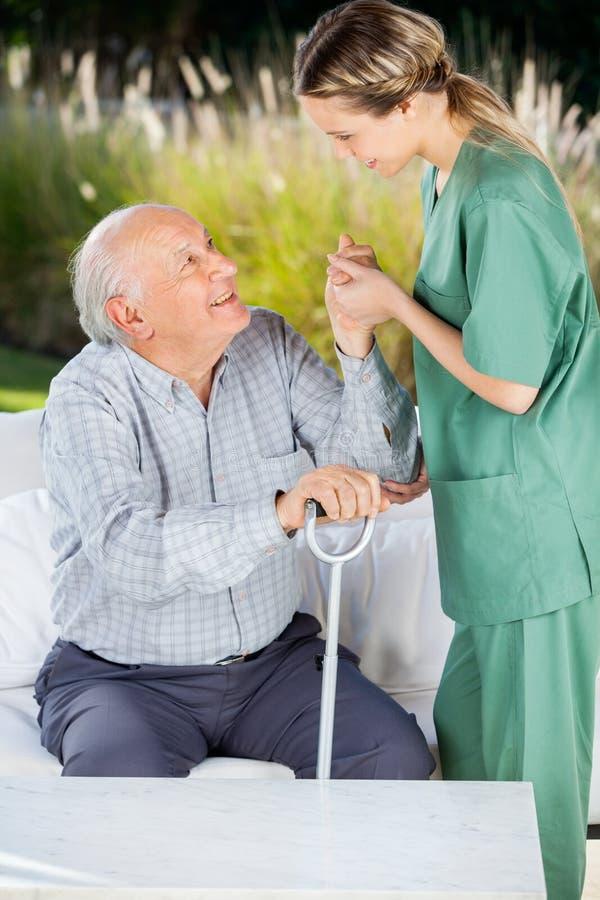 Gardien féminin aidant l'homme plus âgé à se lever photos stock