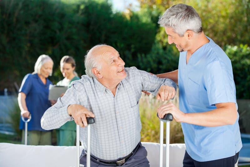 Gardiens masculins et féminins aidant les personnes âgées images libres de droits