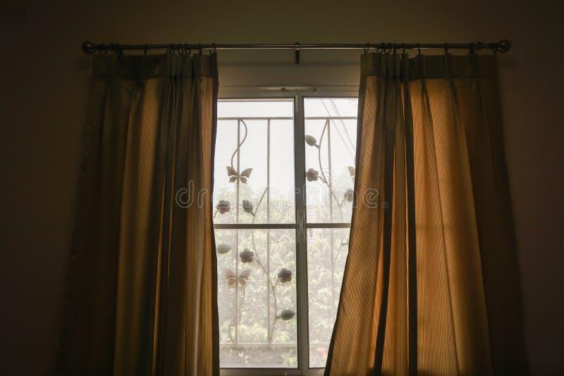 Gardin på sovrumfönstret med morgonsolljus i ferier royaltyfri foto