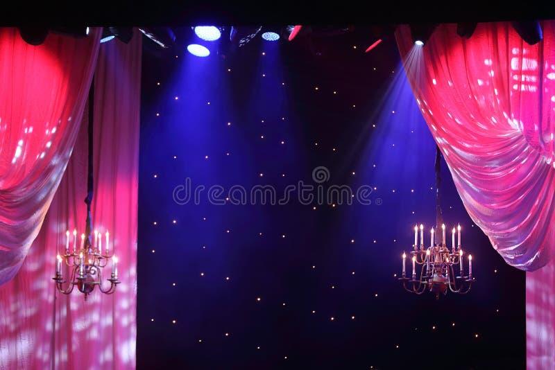 Gardiner med belysning och ljuskronor som hänger i teater. royaltyfri fotografi