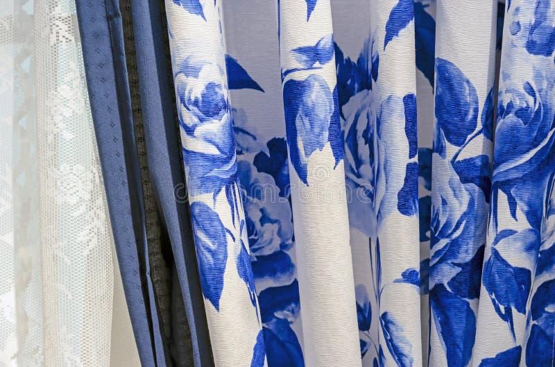 Gardiner med den blåa blom- modellen och den vita tyllen på fönstren av vardagsrummet royaltyfria bilder
