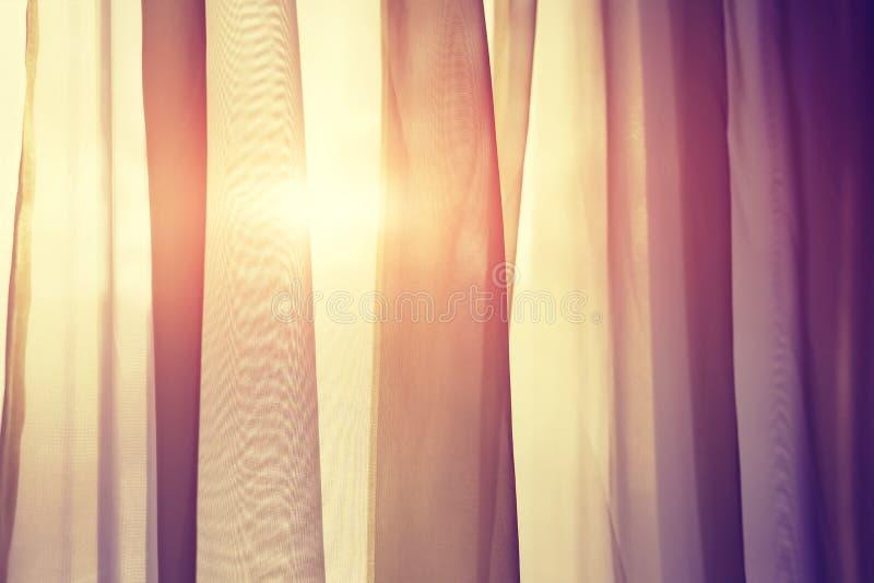 Gardiner på fönster med solen Solen skiner till och med gardiner på solnedgångslutet upp royaltyfri bild