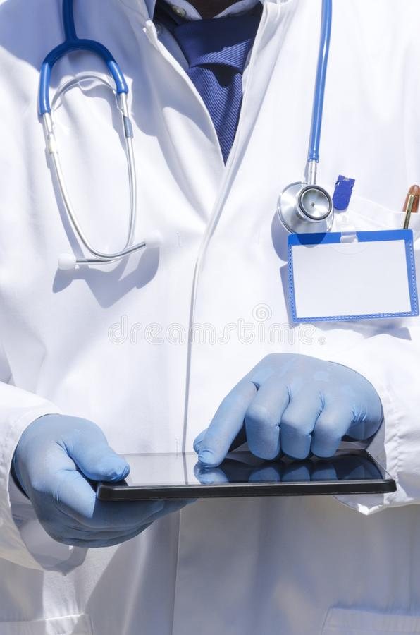 Gardiologist using devise during his work.Vertical shot.Doctor wearing white coat,holding tablet and using it. Doctor wearing laboratory coat and using tablet stock photo