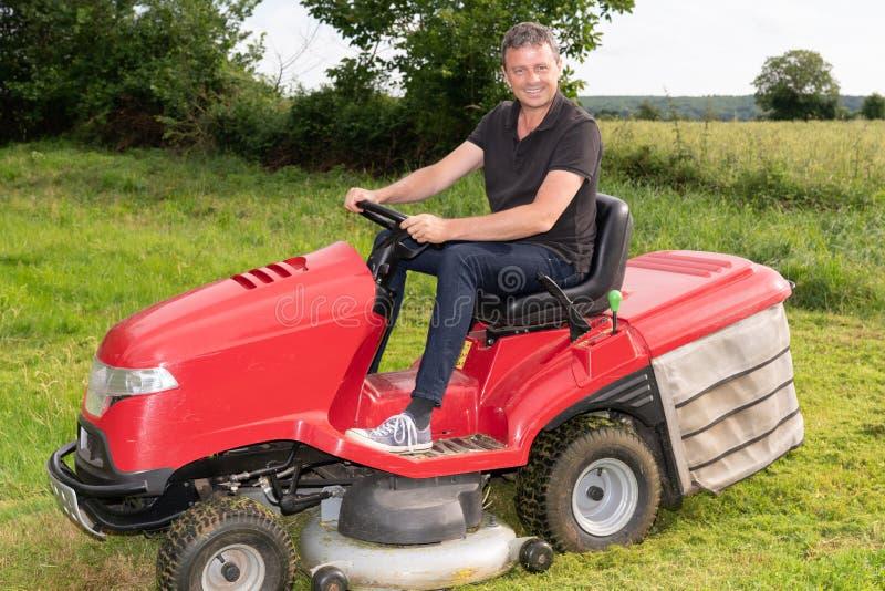 Gardner man on ride-on lawn mower gardener in garden stock photo