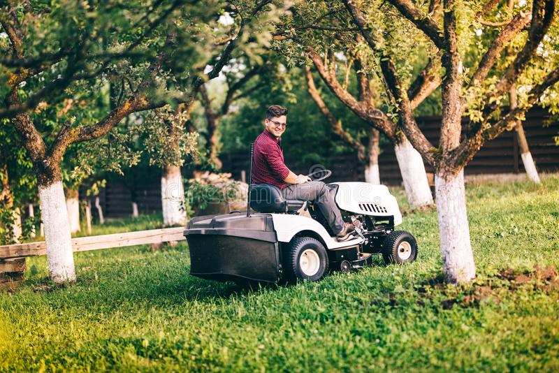 Gardner working and cutting grass in garden. Detail of landscaping works with lawnmower stock photo