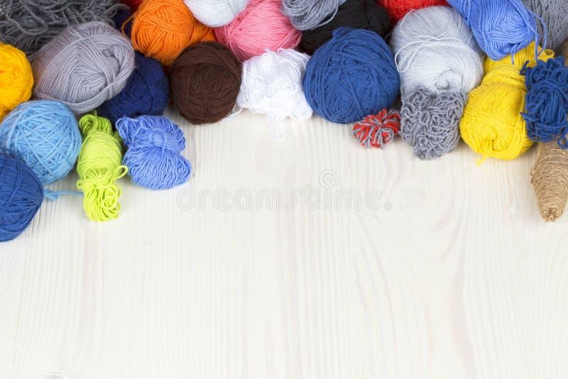 Garen van verschillende kleuren in verwarring op een lichte houten oppervlaktewi stock afbeelding