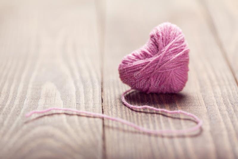 Garen van wol in het symbool van de hartvorm op houten stock afbeelding