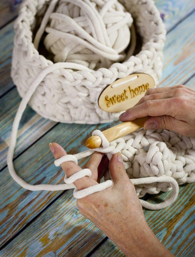 Garens in mand met haaknaalden in harmonische kleuren breien, die levering haken royalty-vrije stock afbeelding