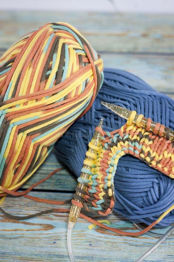 Garens in mand met haaknaalden in harmonische kleuren breien, die levering haken stock fotografie