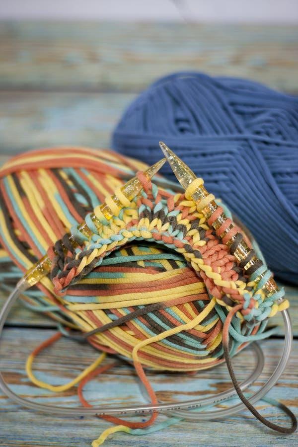 Garens in mand met haaknaalden in harmonische kleuren breien, die levering haken stock foto