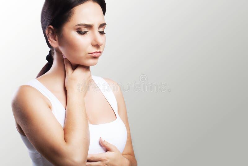 Garganta dolorida Mujer enferma, mujer hermosa joven de la gripe con la garganta dolorida Sensación doloroso en la garganta El co imagenes de archivo