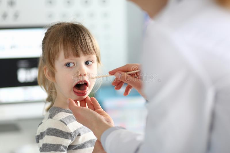 Garganta paciente de examen del ni?o del pediatra de sexo femenino con el palillo de madera imagen de archivo