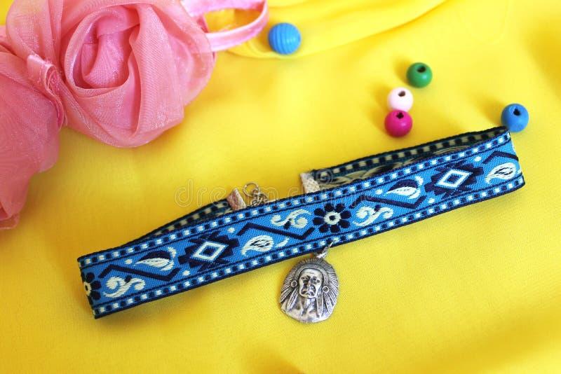 Gargantilha azul dos acessórios feitos a mão com um pendente de prata em um fundo amarelo fotos de stock