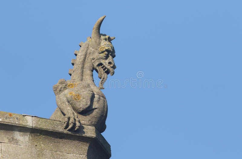 A Gargoyle against a blue sky. An architectural Gargoyle against a blue sky stock photo