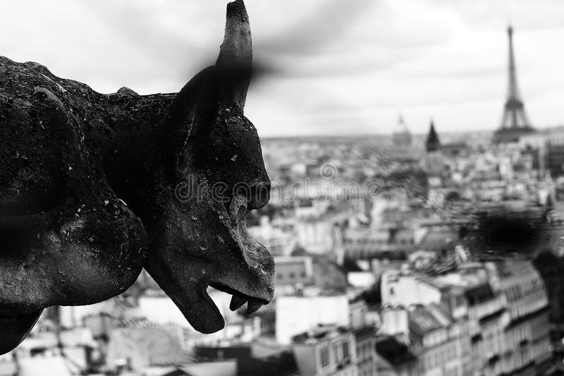 Gargoyle the mythical winged monster on the cathedral of Notre D. Terrifying statue of a gargoyle the mythical winged monster on the cathedral of Notre Dame in stock photography