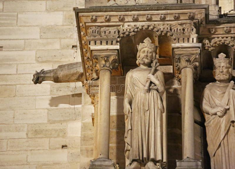 Gargoyle and other statues of the facade of the church of Notre. Dame at night in Paris in France stock photos