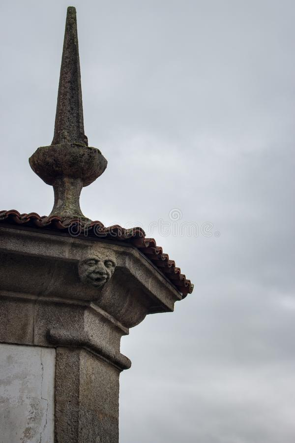 Gargoyle sculpture on medieval church spire against cloudy sky. Ancient gothic architecture concept. Gargoyle face on dame portal. royalty free stock photos