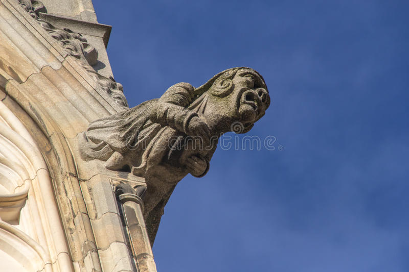 Gargoyle York Cathedral. A Gargoyle on the main tower of York Cathedral with blue sky behind stock photos