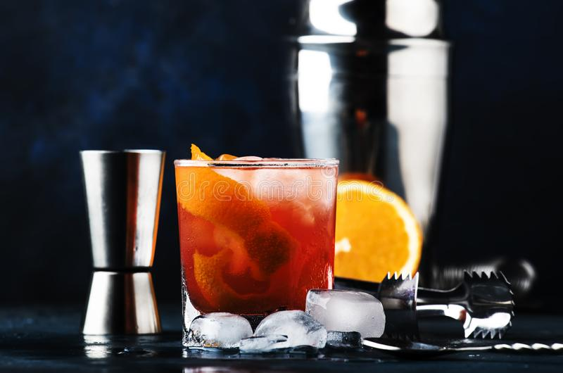 Garibaldi alcoholic cocktail with red bitter, orange juice, zest and ice. Dark blue background, bar tools, selective focus royalty free stock images