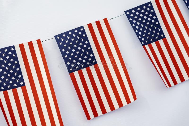 Garland of american flags of rectangular shape close-up on light background, banner design. Fest, city street holiday royalty free stock photography
