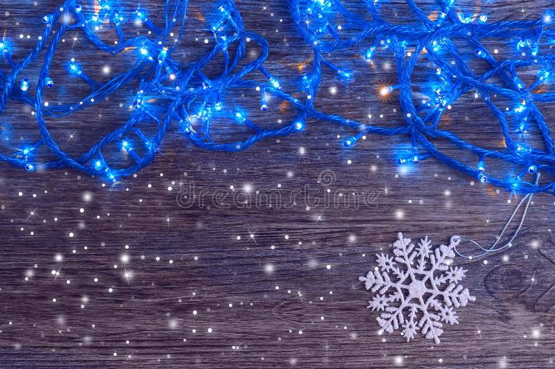 Garland with blue lights and a white snowflake on a wooden background. Christmas and New Year background. royalty free stock images