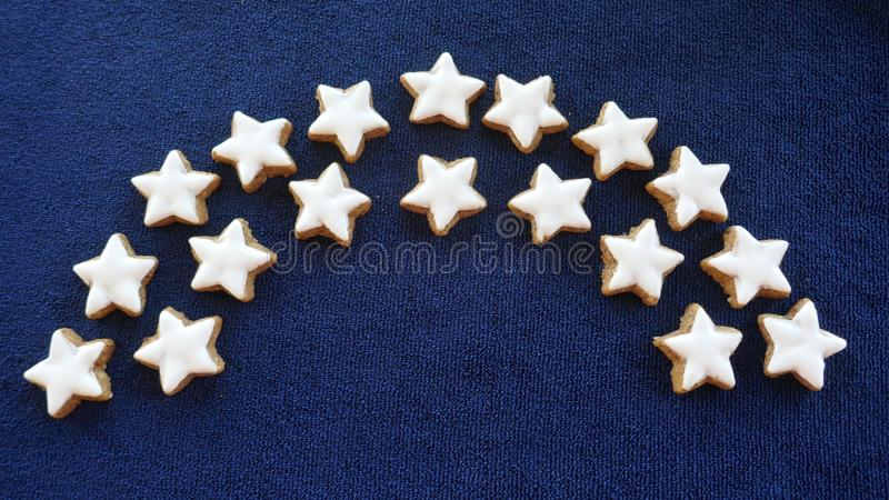 Garland of Christmas cookies. A bow of home-baked cinnamon stars,  against a blue background. royalty free stock photos