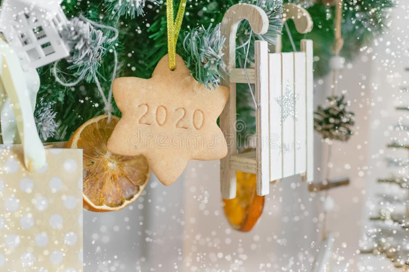 Garland of Christmas tree branches, toys, dried oranges and star shaped cookies. with the number 2020 stock photography