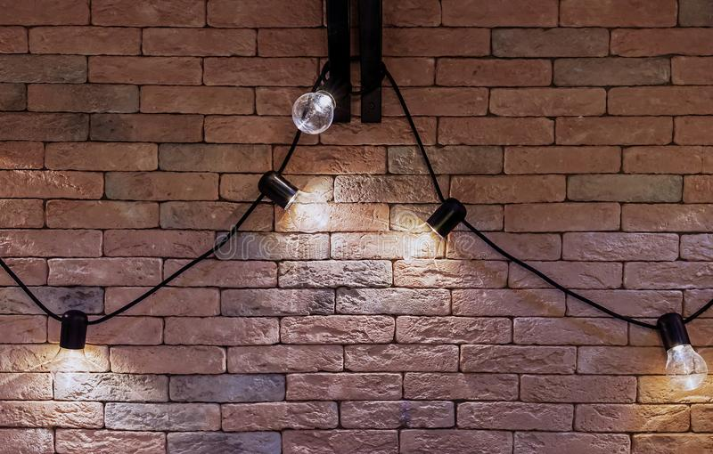 Garland of electric lamps on a brick wall background. Loft style interior royalty free stock images