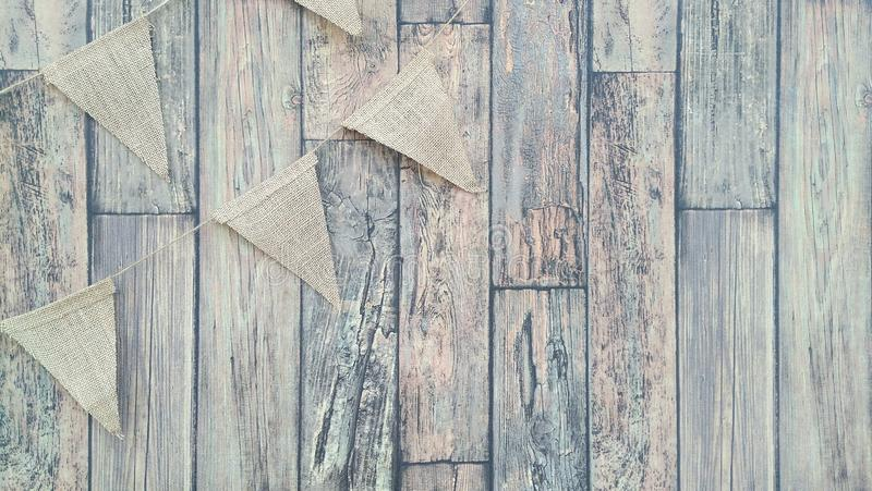 Garland of flags on a wooden wall background. Flags from canvas on a thread. Garland on a wooden wall background stock photography