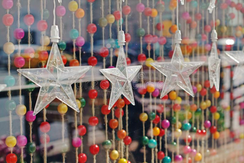 Garland in the form of large transparent stars on a background of colorful beads on ropes royalty free stock photos