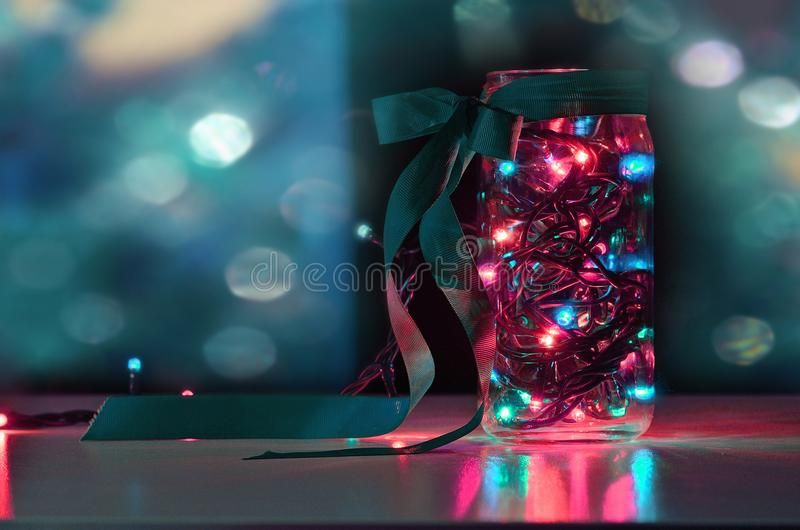 garland in the jar with colorfull ligh on the background of prism light stock photo