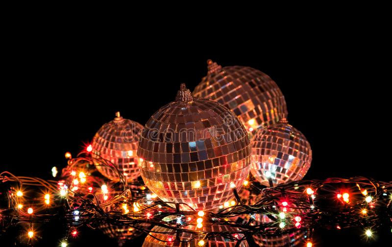 Garland lights and set of mirrored balls on black background. Garland lights and a set of mirrored balls on a black background royalty free stock photos