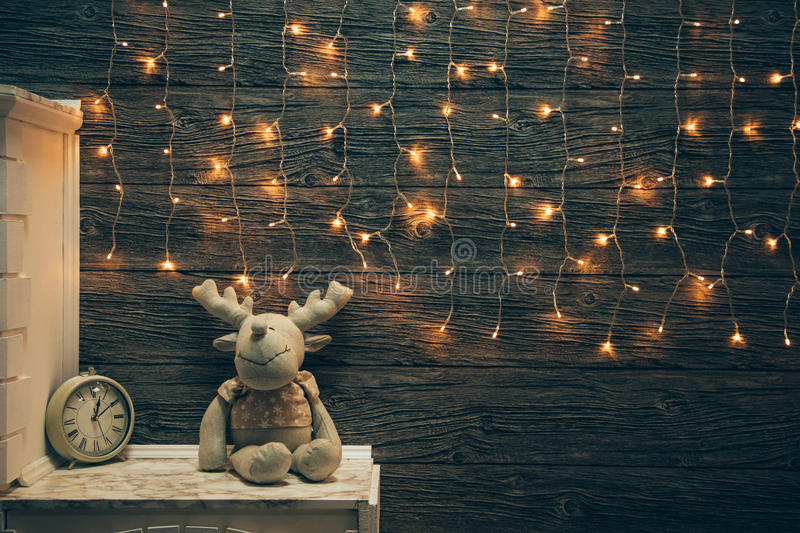 Garland Lights, toy deer, alarm clock on old grunge wooden board. Christmas and New Year decoration. Christmas lighting on wooden planks stock images