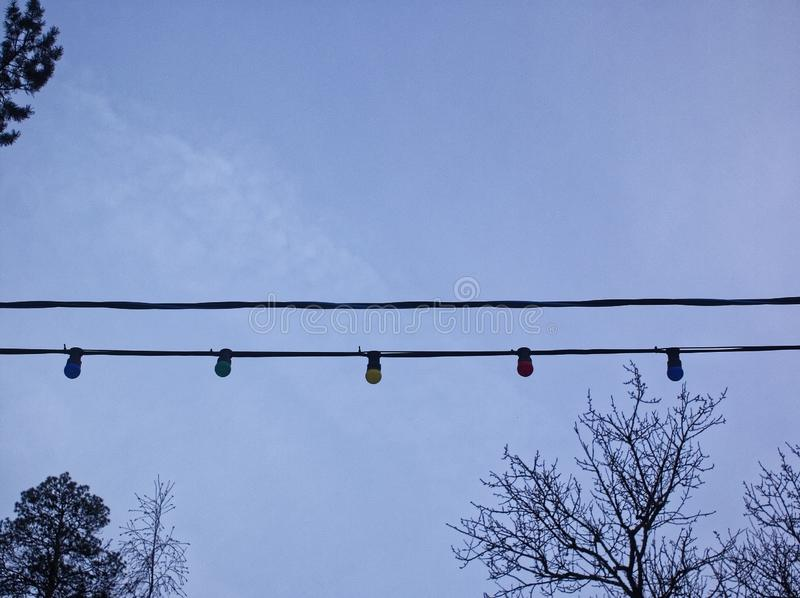 Garland of the switched-off multi-colored bulbs against the cloudy sky. Moscow stock image