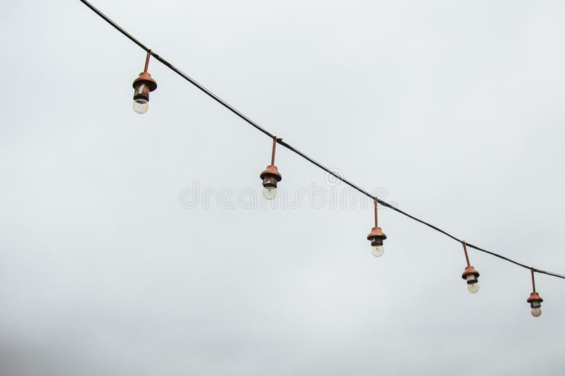 A garland of white light bulbs hanging against a gray sky outdoor. close-up street lighting, copy space.  stock images