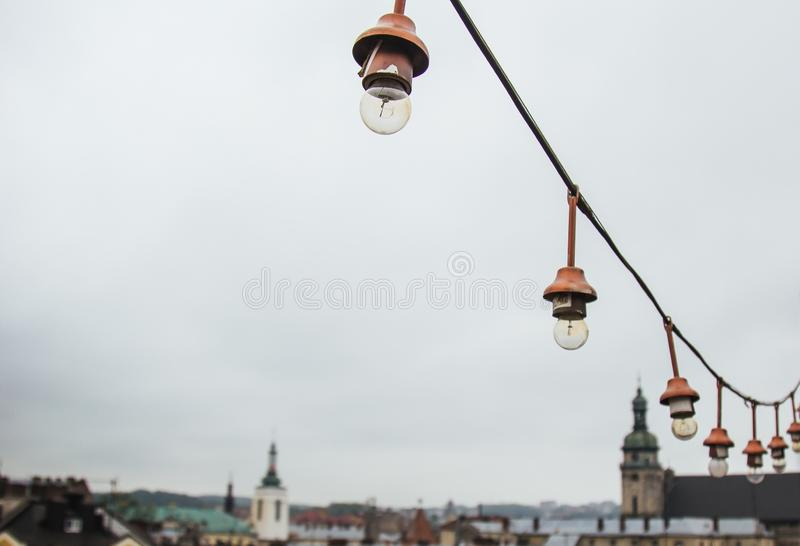 A garland of white light bulbs hanging against a gray sky outdoor. close-up street lighting, copy space.  royalty free stock photography
