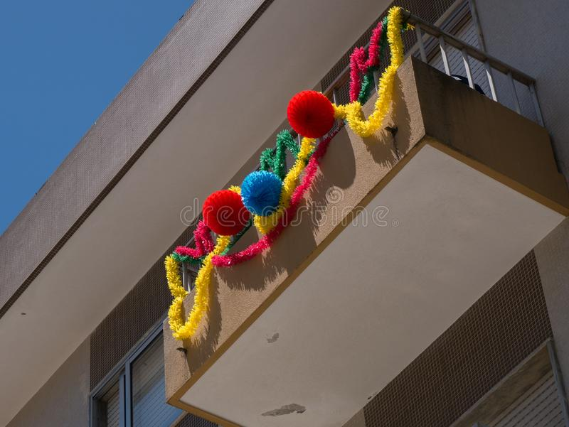 Garlands hang from balconies in Portugal to commemorate Portugal`s Saints day. Colourful garlands hang from balconies in Portugal, in the colours of the stock photography