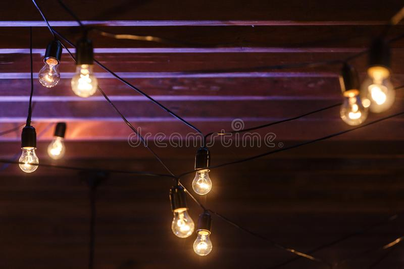 Garlands of yellow bulbs hanging under a purple wooden ceiling royalty free stock images