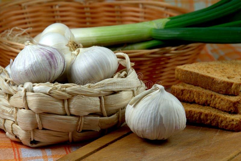 Garlic. Still Life with Garlic and wicker basket royalty free stock image