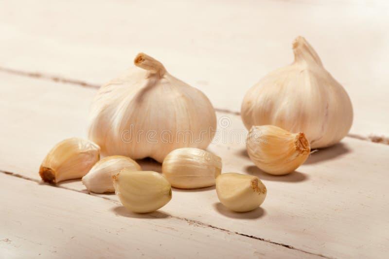 garlic alho cortado, cravo-da-?ndia de alho, bulbo do alho no fundo de madeira branco do vintage imagem de stock royalty free