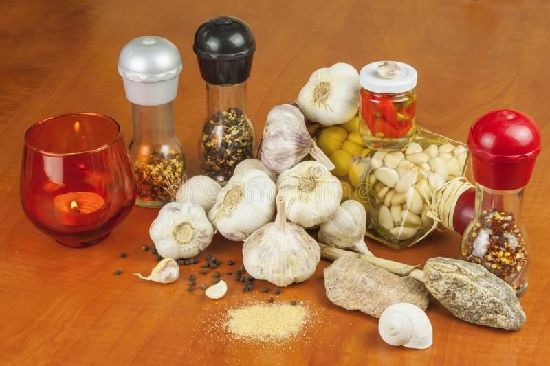 Garlic, aromatic ingredients for flavoring food. Home remedy for colds and flu. Garlic marinated in olive oil. Seasoning food. Preparing for the garden party stock images