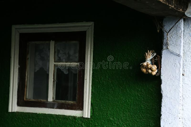 Garlic braid hanging. On a wall of a house in Moldova stock photo
