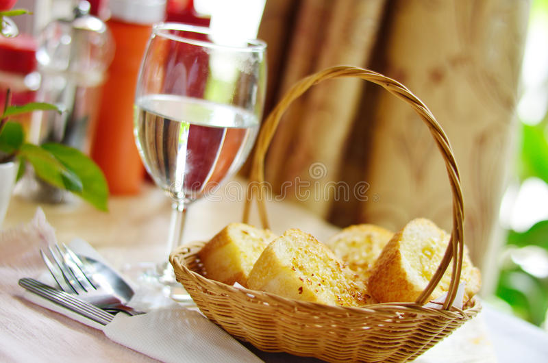 Garlic bread on basket. With drink water stock image