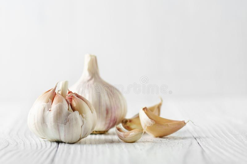 Garlic bulb with garlic cloves over white wood. royalty free stock photography