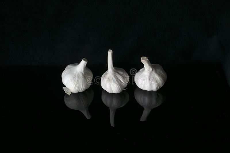 Garlic bulbs. On a black background with reflections royalty free stock photos